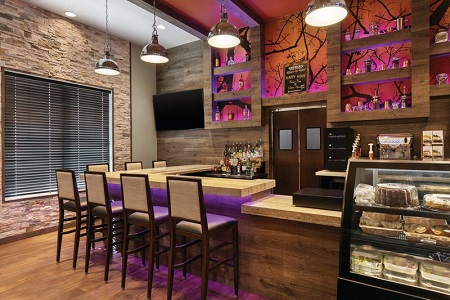 On-site bar with cakes, pastries, a flat-screen TV, and purple and pink lighting