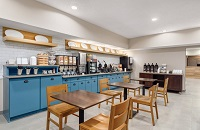 Breakfast room with seating, blue cabinets, cereal, two waffle irons and a coffee station