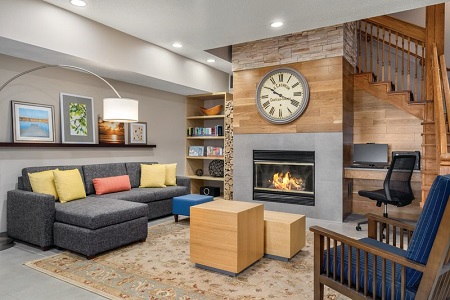 Welcoming hotel lobby with a sectional, armchair, fireplace and business center