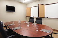 Boardroom with two whiteboards and a TV