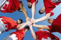 Baseball players putting their hands together in a team huddle