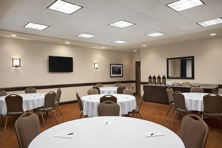 Meeting space with round tables and beverage station
