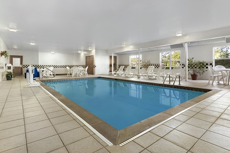 Indoor pool surrounded by white lounge chairs