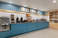 Breakfast servery with blue cabinets, two waffle irons and a waffle mix dispenser
