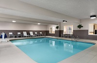 Indoor pool area with white patio furniture against the wall