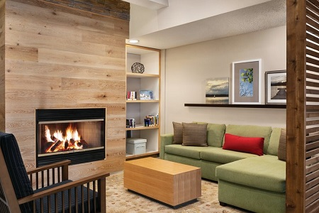 Modern hotel lobby with an armchair, a sectional and a fireplace