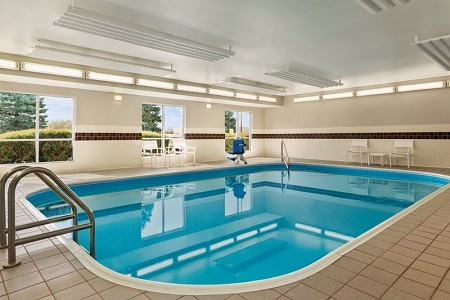 Indoor pool area with white patio chairs