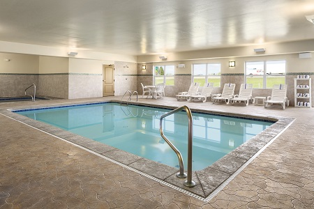 Indoor heated pool beside the hot tub and white lounge chairs
