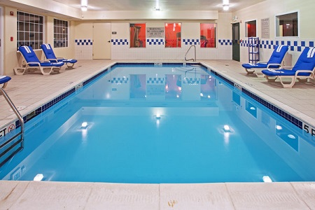 Indoor pool with blue lounge chairs and view of the fitness center