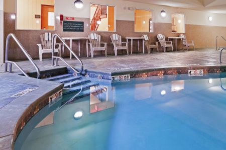 Indoor pool surrounded by tables and chairs