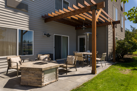 Patio area with a stone fire pit and seating under a wooden pergola