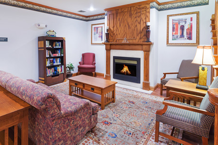Hotel lobby with fireplace, books, couch and chairs