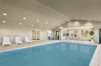 Indoor pool area with white lounge chairs