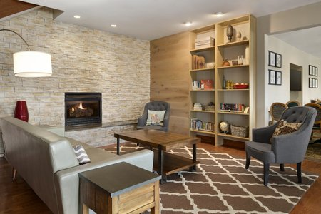 Comfortable hotel lobby with fireplace, seating and a patterned rug