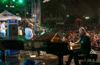 Piano and musicians on a stage with a crowd watching