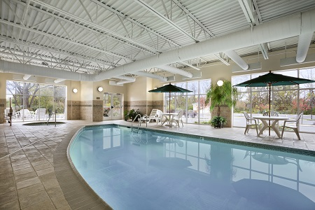 Indoor pool and hot tub area with green umbrellas