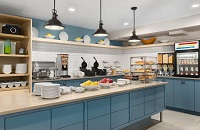 Breakfast servery with blue cabinets, assorted cereals and a make-your-own waffle station