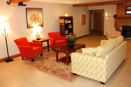 Comfortable lobby with patterned couch and red armchairs