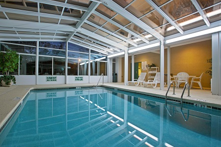 Indoor Pool With Windows And Deck Chairs