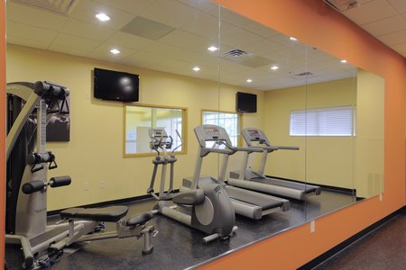 On-site fitness center with TVs and mirror