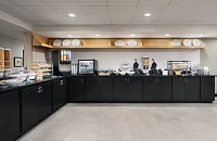 Breakfast room with black cabinets, pastries, juice and a make-your-own waffle station