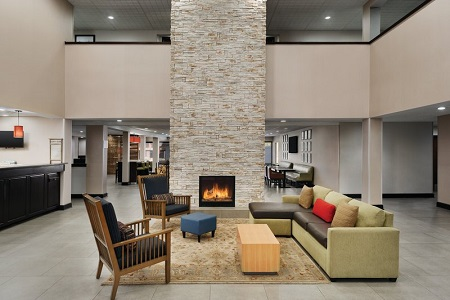 Hotel lobby with two armchairs, a sectional and a stone fireplace
