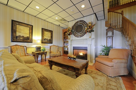 Lobby with fireplace, staircase, couch and chairs
