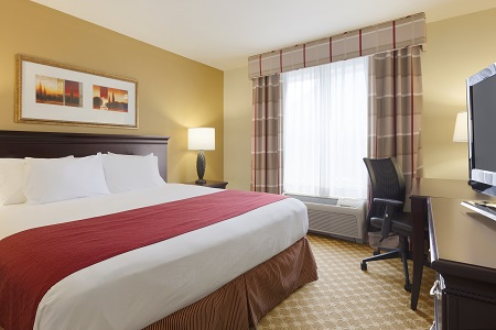 Sumter hotel room with king bed, brown curtains and work desk