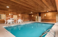 Indoor pool area with white patio furniture and wood paneling on the walls and ceiling