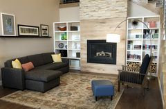 Welcoming hotel lobby with a modern fireplace and bookshelves