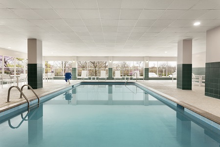 Indoor pool with green tiles and lots of natural light