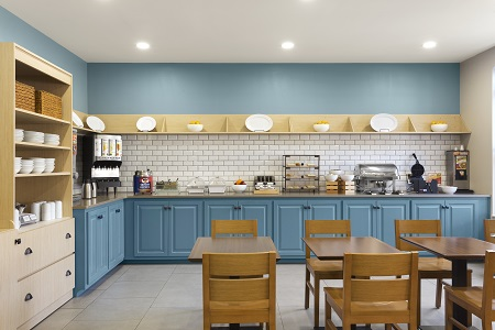 Hotel's breakfast room with light blue cabinets and real diningware