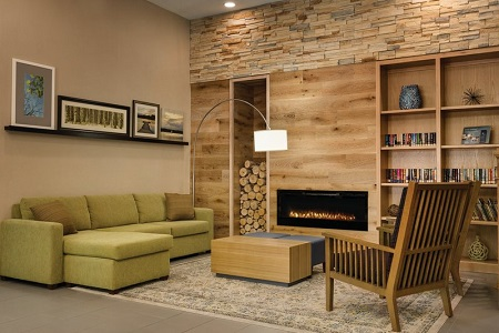 Hotel lobby with fireplace, armchair and green sectional