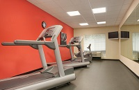 Fitness center with two treadmills, a recumbent bike and a red accent wall