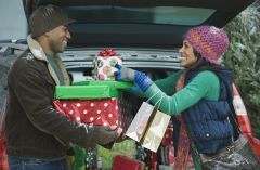 Smiling couple unloading a trunk full of gifts