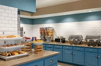 Breakfast servery with blue cabinets, fresh fruit, and assorted breads and pastries