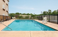 Sparkling outdoor pool with patio furniture and a pool lift