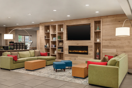 Hotel lobby with two green sectionals, a coffee station and a flat-screen TV mounted above the fireplace