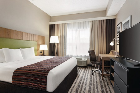 Hotel room with a king bed, a work desk and a flat-screen TV