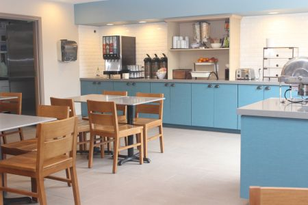 Breakfast room featuring blue cabinets, a coffee station and rotating breakfast items