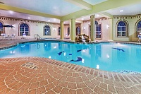 Indoor pool area with a waterfall feature and hot tub