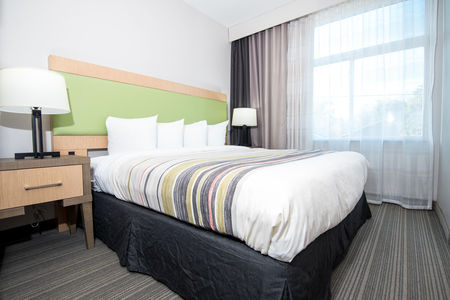 Guest room featuring a king bed with striped linens