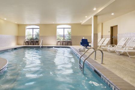 Indoor pool area with lounge chairs and arched windows