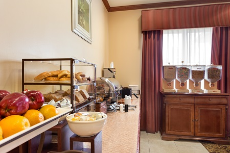 Hotel breakfast area with fresh fruit, bagels and cereal