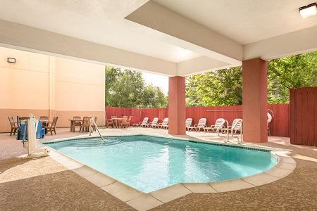 Houston, TX hotel's sparkling outdoor pool with covered seating area