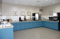 Breakfast servery with blue cabinets, hot entrées and assorted cereals