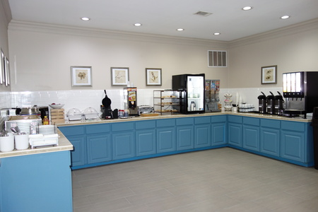 Breakfast servery with blue cabinets, hot meal options and assorted beverages