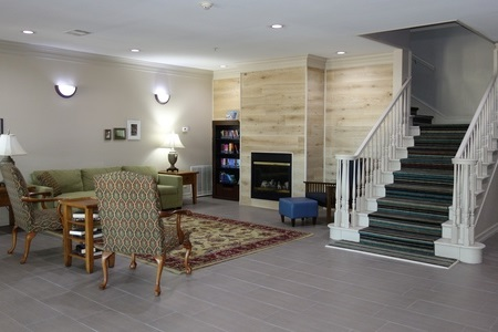 Welcoming hotel lobby featuring a fireplace, a patterned rug and a green couch