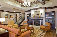 Hotel lobby with a fireplace, a couch and three patterned armchairs