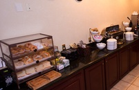 Bagels, muffins, pastries and other breakfast items set up on the bar